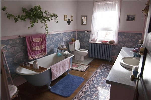 Large upstairs bathroom with original antique bathtub for a soothing soak at Historic Reesor Ranch.