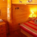 Bunkhouse queen bedroom lined with Cypress Hills lumber and upright log at Historic Reesor Ranch.