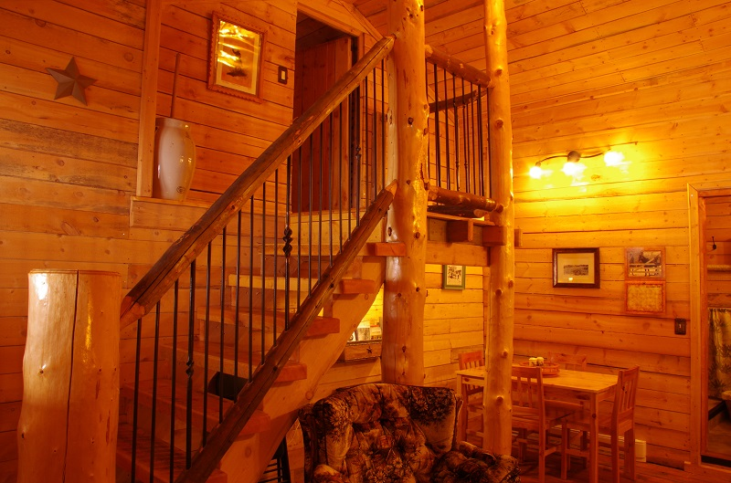 Log stair case to loft in Bunkhouse bedroom at Historic Reesor Ranch.