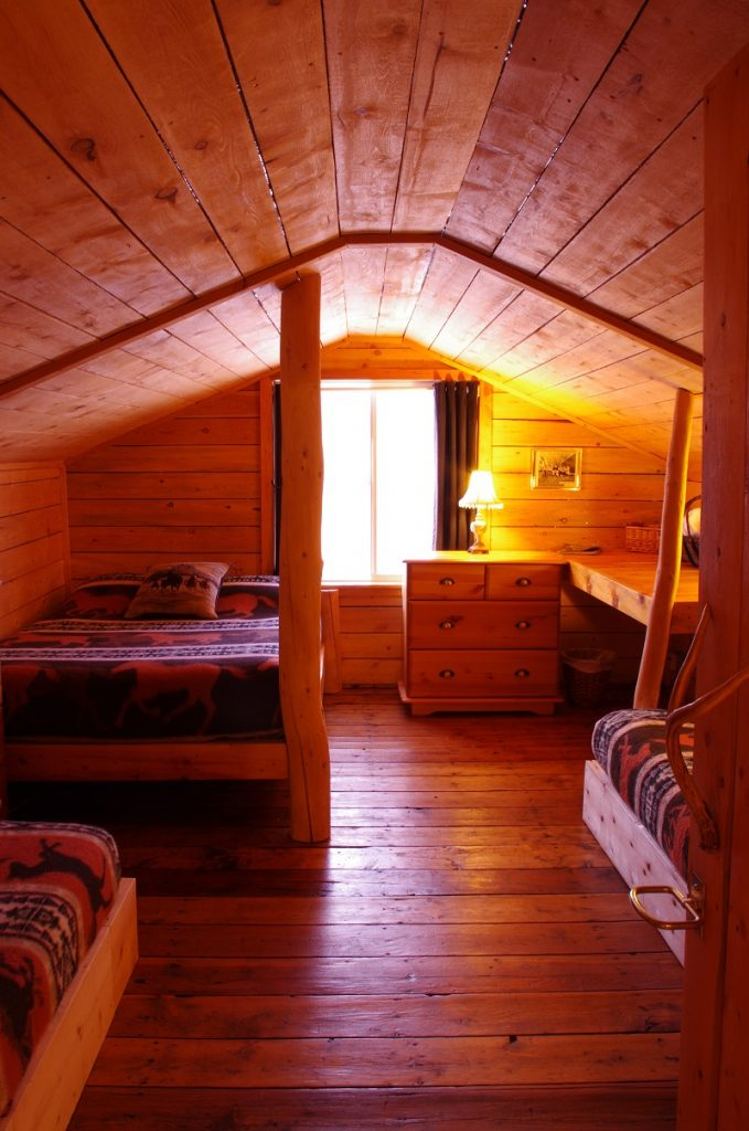 Bunkhouse loft bedroom - one double & two twin beds. Check out the original pine floor in this room that housed ranchhands at the Historic Reesor Ranch in the early 1900's.