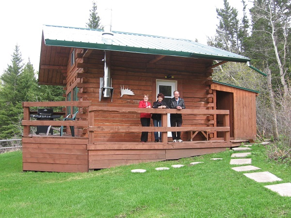 Welcome! Log cabin side deck entry and woodshed at Historic Reesor Ranch.